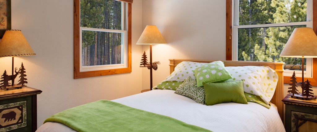 Main floor bedroom — all new luxury bedding and a view to the surrounding pines